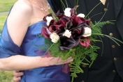 Hand tied wedding bouquet with burgundy calla lilies, bear grass, fern and white roses