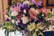 Table arrangement. Iris, lime green spray chrysanthemums, Singapore orchids, gypsophila, roses, spray carnations, lisianthus, freesias, purple mauve, white tones.