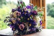 Wedding bouquet hand tired. Iris, lime green spray chrysanthemums, gypsophila, roses, spray carnations, lisianthus, freesias, purple mauve, white tones.