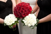 Wedding posies with red and white roses and camellia leaves