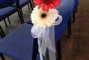 Pew wedding flowers - white ribbon with red and white gerberas