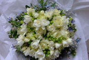 Hand tied wedding bouquet with cream freesias, cream roses and blue tweedia