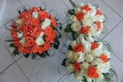 Wedding posies with white and orange roses with diamonds and camellia leaves