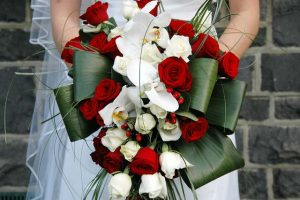 Trailing wedding bouquet with red roses with phalaenopsis orchids