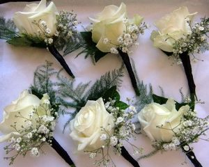 White rose button holes with gypsophila