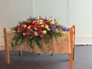Wedding table floral church arrangement with trailing ivy, blue irises, yellow carnations, red gerberas