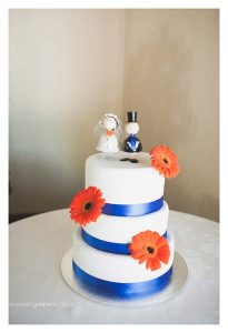 Wedding cake floral decorations with orange gerberas